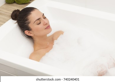 Beautiful young woman is taking a bath..