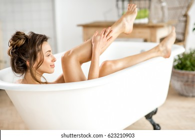 Beautiful young woman taking care about legs lying in the bathtube in the bathroom
