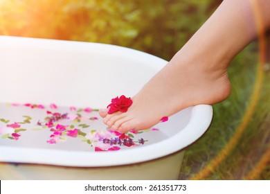 Beautiful young woman taking a herbal bath.