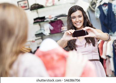 A beautiful young woman taking a photo of her friend at a boutique.