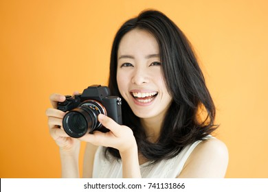 Beautiful young woman taking photo with digital camera, against orange background.