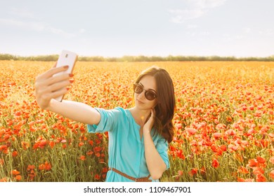 Beautiful young woman taking selfie with smartphone on background of red poppies meadow on sunny summer day.