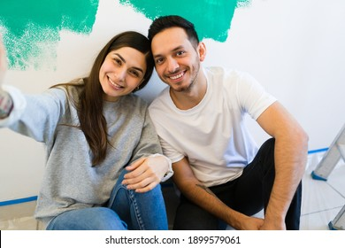 Beautiful young woman taking a selfie with her smartphone along her handsome boyfriend after moving into their new home