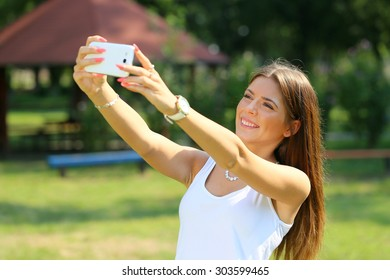 beautiful young woman taking selfie photo in the park with a smartphone