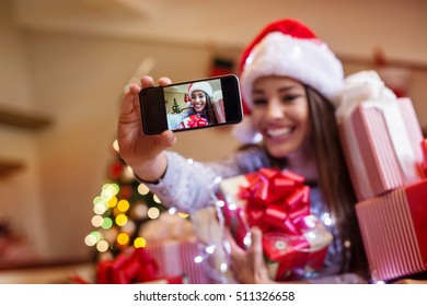 Beautiful young woman taking selfie with smartphone. Christmas mood.