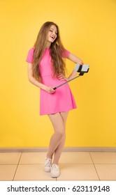 Beautiful young woman taking selfie near color wall