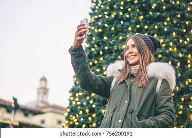 Beautiful young woman taking a selfie with christmas tree behind her with mobile phone camera - Pretty girl enjoying christmas holidays taking a self photography in the city with her smartphone