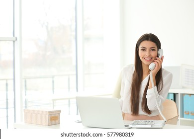 Beautiful young woman talking by telephone while working in office