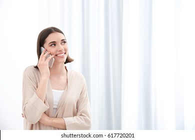 Beautiful young woman talking by mobile phone indoors
