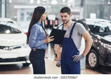 Beautiful young woman is talking to handsome car mechanic while repair a car in dealership.