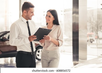 Beautiful young woman is talking to handsome car dealership worker while choosing a car in dealership