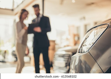 Beautiful young woman is talking to handsome bearded sales manager while choosing a car in dealership