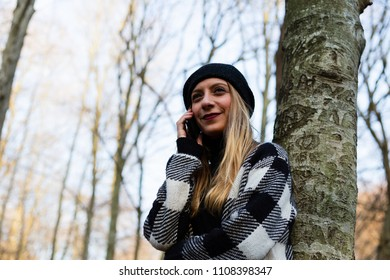 Beautiful young woman talking on phone in park, smiling (selective focus)