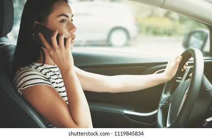 Beautiful young woman talking on phone while driving the car.
