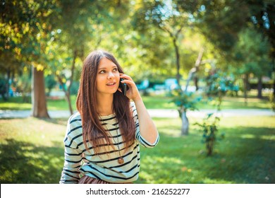 Beautiful young woman talking on a phone in city park.