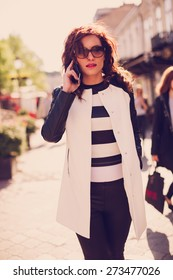 Beautiful young woman talking on mobile phone on the street