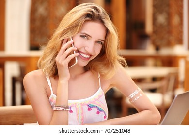 Beautiful young woman talking on mobile phone in cafe