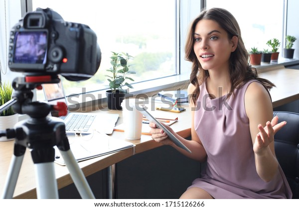 Beautiful young woman talking and smiling while making new video for her blog.