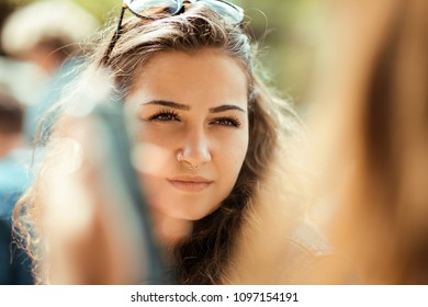 beautiful young woman talking to somebody, outside in the sunlight, happy smiling, lifestyle concept shoot