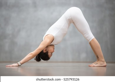 """Beautiful young woman with tattoo on foot meaning """"Wild cat"""" working out in white sportswear against grey wall, doing yoga or pilates exercise. Downward facing dog, adho mukha svanasana. Full length"""