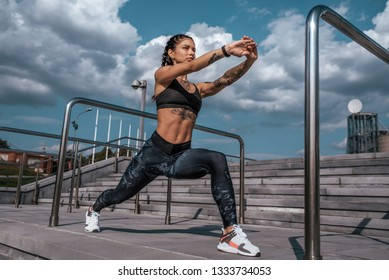 Beautiful young woman in tattoos, sportswear, leggings and top. In the summer in the city, training the muscles of the legs, warming up before fitness, workout in the city before jogging.