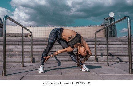 Beautiful young woman in tattoos, yoga pose, sportswear, leggings and top. In the summer in the city, training of muscles of flexibility, warming up before fitness, workout in city before jogging.