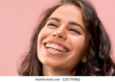 Beautiful young woman with teeth braces on pink