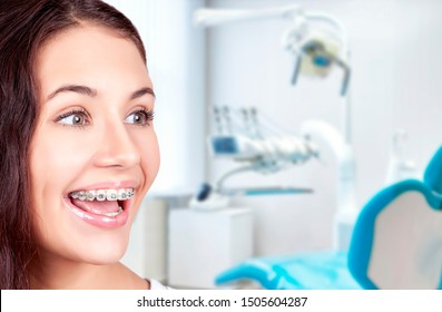 Beautiful young woman with teeth braces in the orthodontist's office.