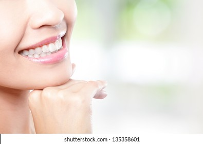 Beautiful young woman teeth close up with copy space on the right side. Isolated over green background, asian beauty model