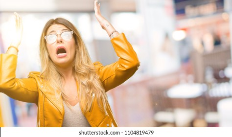 Beautiful young woman terrified and nervous expressing anxiety and panic gesture, overwhelmed at restaurant