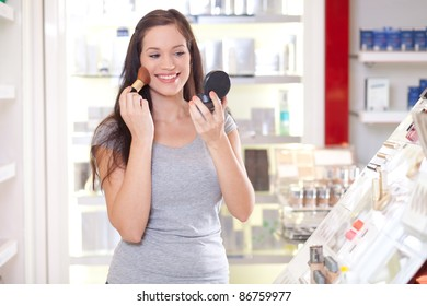 Beautiful young woman testing make up in a drug store
