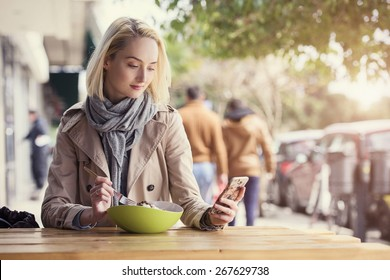 beautiful young woman is texting on her smartphone while eating a salad