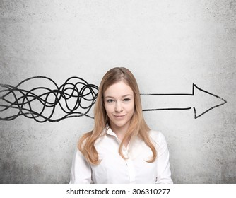 Beautiful young woman is thinking about concept of business development. A huge arrow are drawn on the concrete wall.