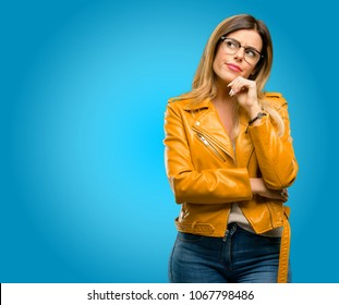 Beautiful young woman thinking and looking up expressing doubt and wonder, blue background