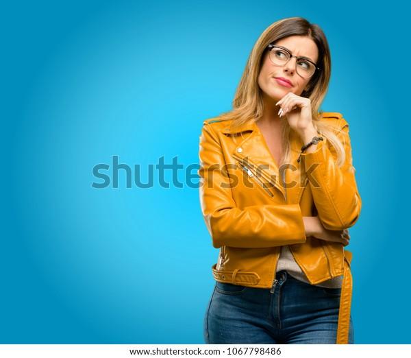 Mujer joven hermosa pensando y mirando para expresar dudas y maravillas, fondo azul