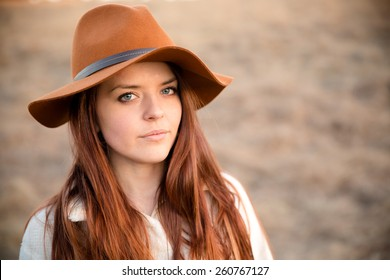 Beautiful Young Woman - This is a portrait of a beautiful young woman wearing a brimmed hat with a serious look on her face.