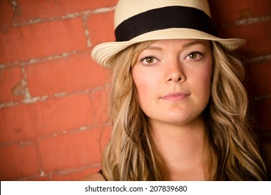 Beautiful Young Woman - This is a shot of a beautiful young woman wearing a fedora against a brick wall.