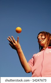 beautiful young woman throwing fresh orange in to air