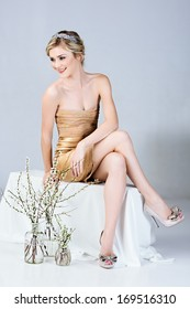 Beautiful young woman in tight gold minidress sitting on studio background