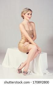 Beautiful young woman in tight gold mini dress sitting on studio background