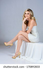Beautiful young woman in tight white wedding dress sitting on studio background