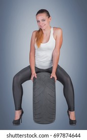 Beautiful young woman with tire in studio