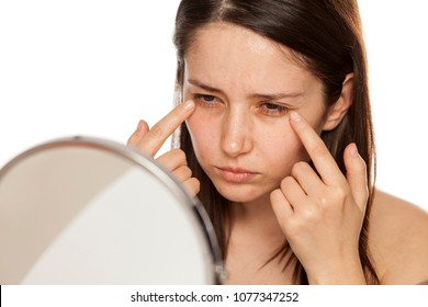 Beautiful young woman touch her face under eyes in mirror on white background