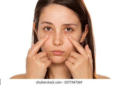 Beautiful young woman touch her face under eyes on white background