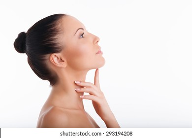 Beautiful young woman is touching her chin with her index finger. She is raising her head up with care. She is serene and composed. Isolated on white background and there is copy space in right side
