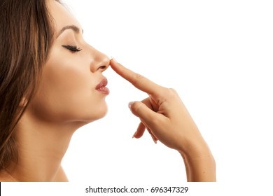 Beautiful young woman touching her nose