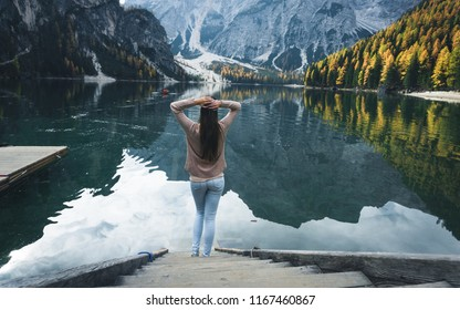 Beautiful young woman tourist on a pier beside a azure mountain lake. Young girl relax and watch high peaks of the Alps above the lake mirror. Autumn 2017, Lago di Braies
