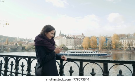 Beautiful Young Woman Tourist In Prague Using Her Smartphone, Travelling Concept