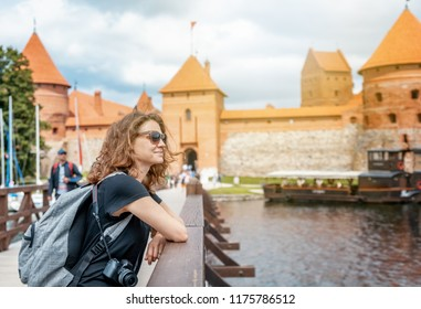 Beautiful young woman tourist traveler in the background Trakai castle on the lake, Lithuania sights, travel to the Baltic countries