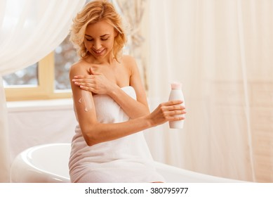 Beautiful young woman in a towel holding a bottle of cream and applying it on arm while sitting in the bathroom.